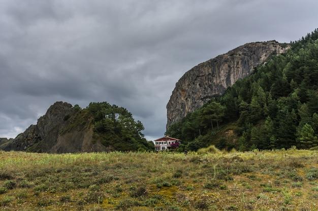 Maison entre collines, une crête et un ciel orageux Photo Premium