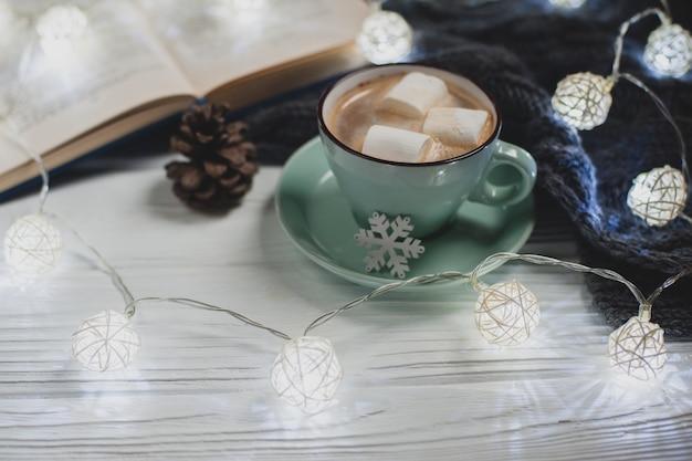 Maison D'hiver Confortable. Tasse De Cacao Avec Des Guimauves, Pull En Tricot Chaud, Livre Ouvert, Guirlande De Noël Sur Une Table En Bois Blanc. Ambiance D'une Agréable Soirée De Lecture. Photo Premium