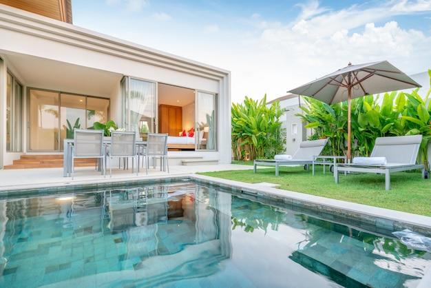 Maison ou maison design extérieur montrant une villa avec piscine tropicale avec jardin de verdure, lit de bronzage, parasol, serviettes de piscine Photo Premium