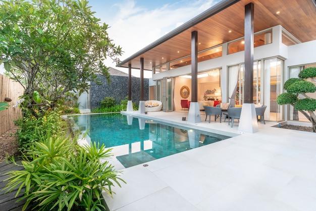 Maison ou maison design extérieur montrant une villa de piscine tropicale avec jardin de verdure, Photo Premium