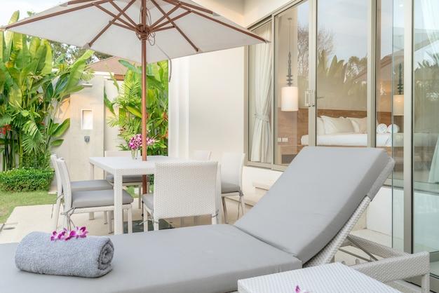 Maison ou maison design extérieur montrant une villa de piscine tropicale avec lit de bronzage, parasol Photo Premium