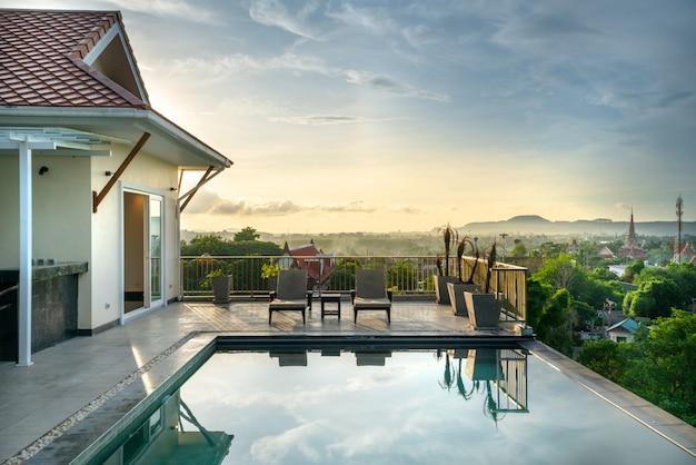 Maison ou maison design extérieur montrant une villa de piscine tropicale avec un solarium Photo Premium