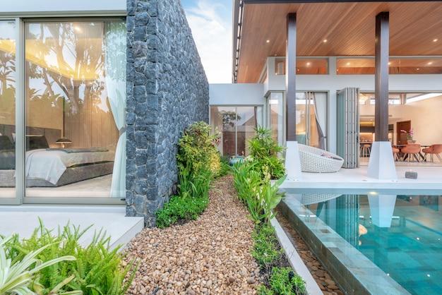 Maison ou maison design extérieur montrant une villa tropicale avec piscine, jardin de verdure et chambre Photo Premium