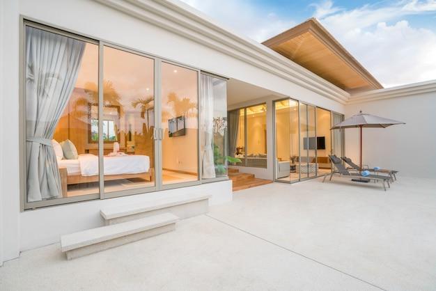 Maison ou maison design extérieur montrant une villa tropicale avec piscine et solarium Photo Premium