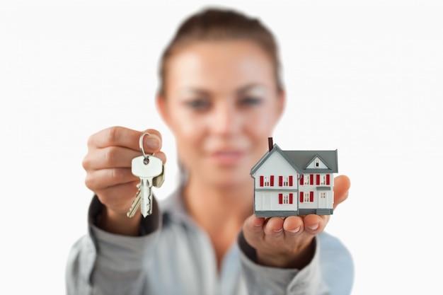 03a3e9076ee8d9 Maison miniature et clés présentées par une femme agent immobilier ...