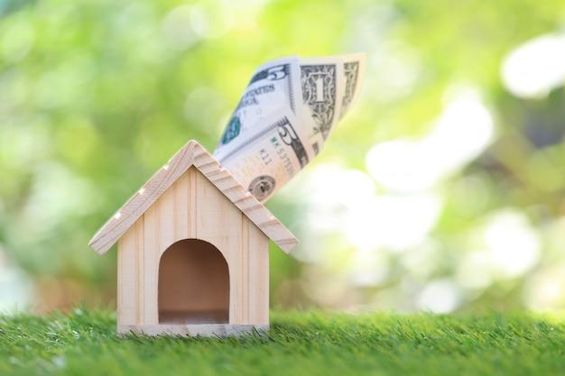 Maison modèle avec billet de banque sur fond vert naturel, épargne pour préparer à l'avenir Photo Premium