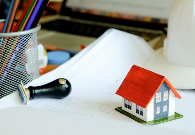 Maison modèle et timbre en caoutchouc sur le plan de la maison sur la table. pour les entreprises commerciales à domicile. Photo Premium