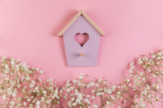 Maison d'oiseau en forme de coeur avec des fleurs de gypsophila décorées sur fond rose Photo gratuit