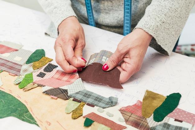 Maison de patchwork de tissu de femme avec aiguille au lieu de travail Photo gratuit