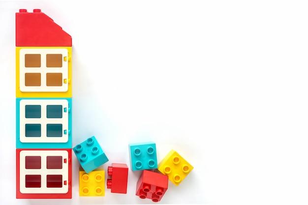 Maison de petites et grandes briques de constructeur en plastique sur fond blanc. jouets populaires. Photo Premium