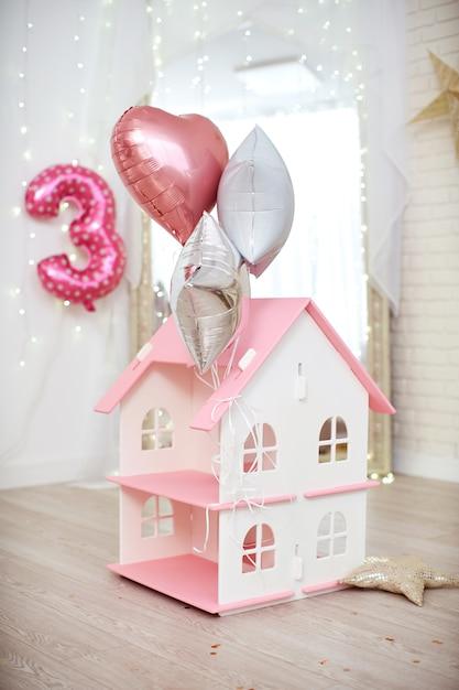 Maison pour jouer avec des poupées au toit rose se dresse sur le sol dans une pièce lumineuse décorée de ballons à l'hélium Photo Premium