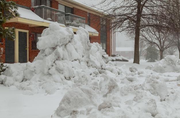 Maison rouge dans la neige avec des arbres à feuilles persistantes Photo Premium