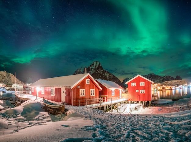 Maison rouge dans un village de pêcheurs avec aurores boréales au-dessus de l'océan arctique en hiver la nuit Photo Premium