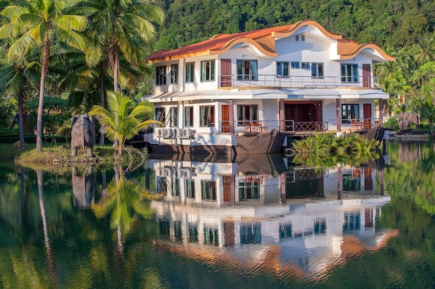 Maison Tropicale Sous La Forme D'un Bateau Dans Un Grand Lagon Avec Des Palmiers Verts Photo Premium
