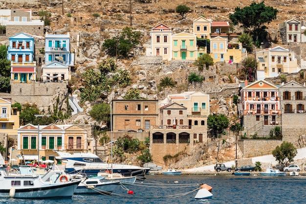 Les maisons colorées traditionnelles et le port de l'île de symi, dans l'état du dodécanèse, en grèce. Photo Premium