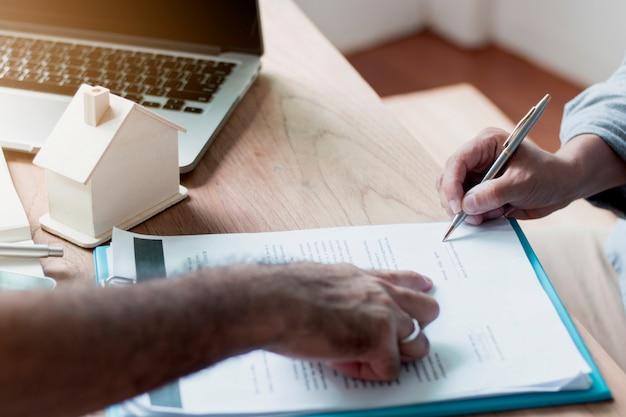 Maisons de succession et signer un contrat, une agence immobilière ou un banquier indiquant à l'acheteur la signature sur papier Photo Premium
