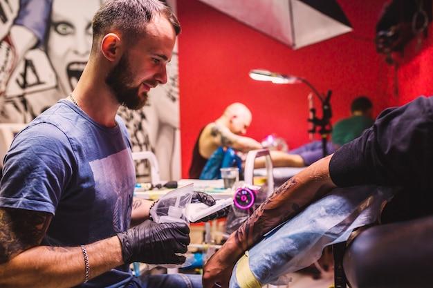 Maître Adulte Dans Le Studio De Tatouage Photo gratuit