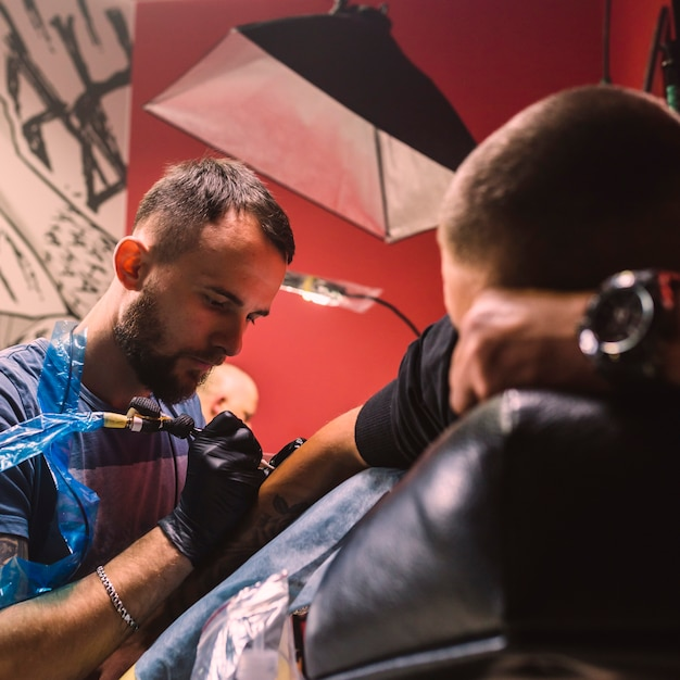 Maître Adulte Faisant Le Tatouage Sur Le Bras Photo gratuit