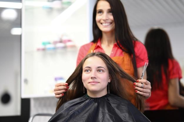 Maître Coiffeur Détient Les Cheveux Du Client Dans Un Salon De Beauté Photo Premium