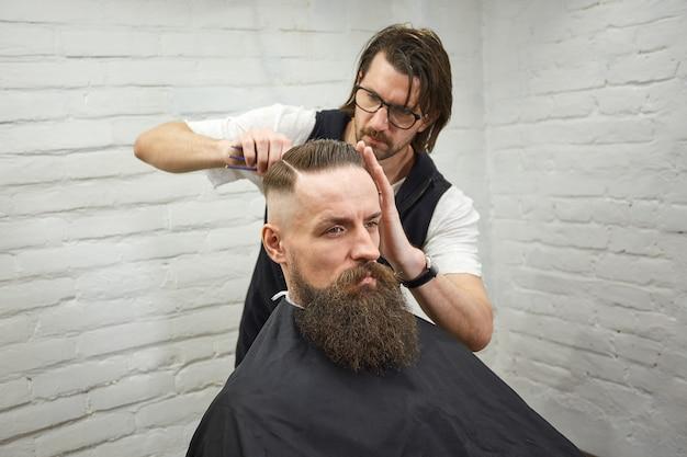 Maître coupe les cheveux et la barbe des hommes dans le salon de coiffure, le coiffeur coiffe un jeune homme Photo Premium