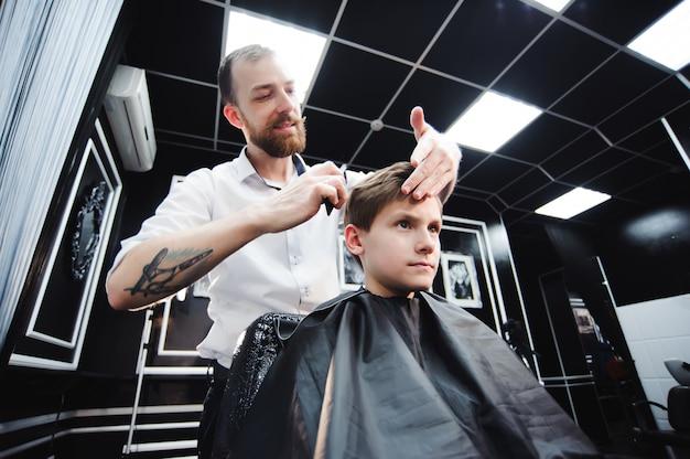 Maître Coupe Les Cheveux D'un Garçon Dans Le Salon De Coiffure Photo Premium