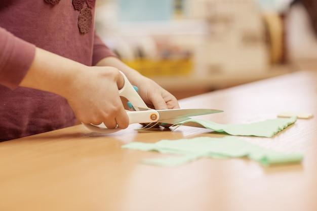 Le maître-couture coupe un morceau de tissu avec des ciseaux pour travailler avec le produit Photo Premium