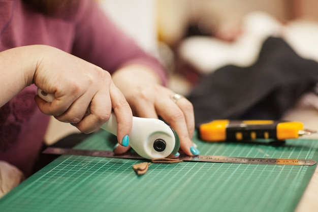 Le maître-couture coupe un morceau de tissu pour un travail ultérieur. Photo Premium