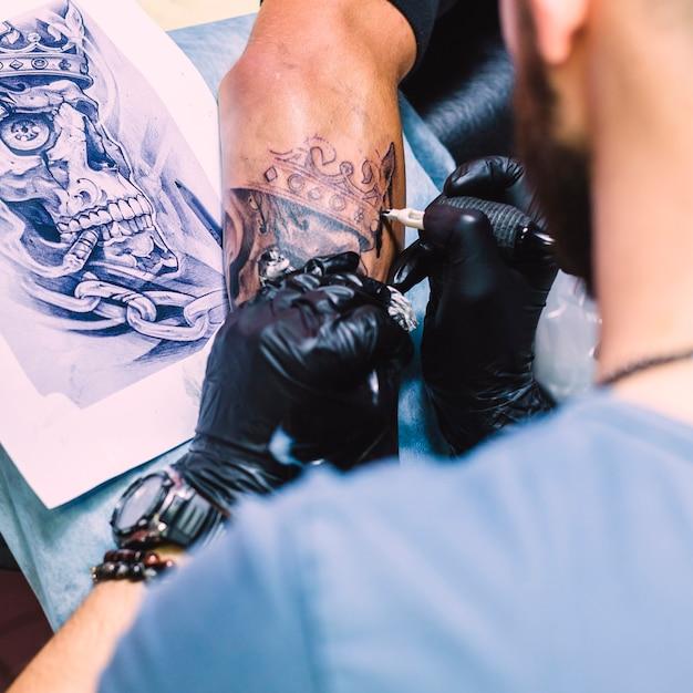 Maître faisant tatouage avec du fer Photo gratuit
