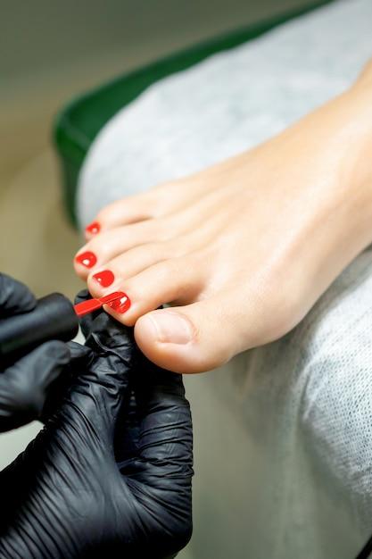 Maître De Pédicure Appliquant Le Vernis à Ongles Rouge Aux Ongles Des Pieds De La Jeune Femme Dans Un Salon De Manucure Photo Premium