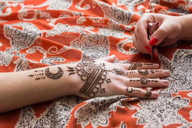 Maître tatouant mehndi peindre sur une main de femme Photo gratuit