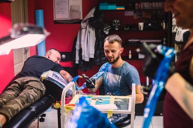 Maîtres Et Clients Dans Un Studio De Tatouage Photo gratuit