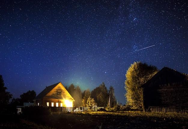 Majestueuse Voie Lactée Et L'étoile Filante Au-dessus De La Maison Du Village En été. Un Ciel étoilé. Photo Premium