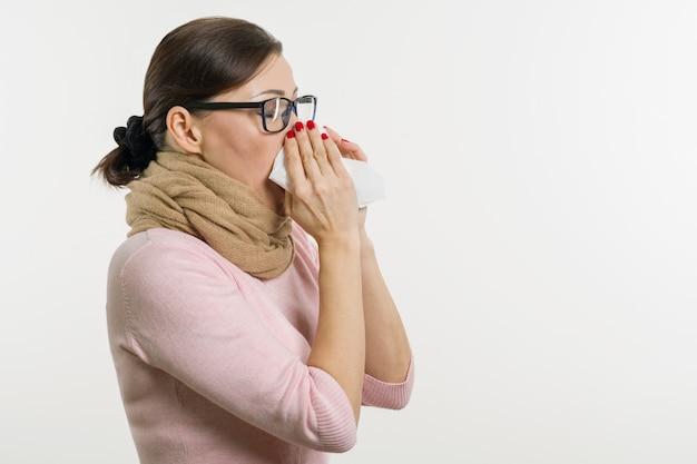 Malade femme tenant un mouchoir, fond blanc Photo Premium