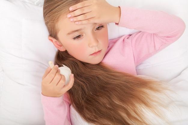 Malade fille sur lit éternuer dans mouchoir dans chambre à coucher Photo Premium