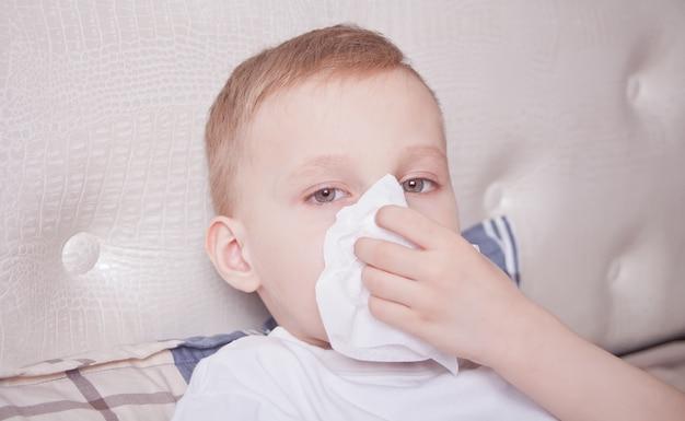 Malade garçon couché dans un lit et se moucher Photo Premium