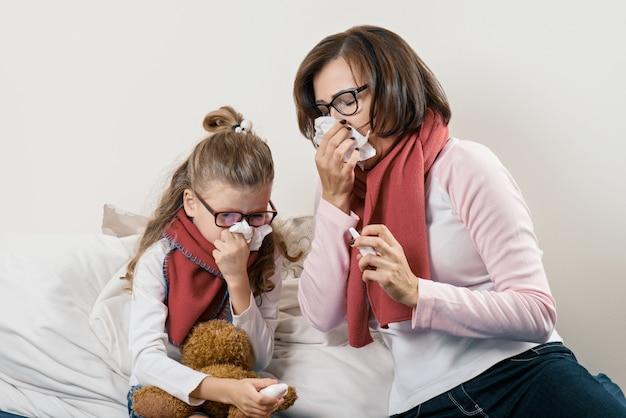 Malade mère et enfant éternuant dans un mouchoir Photo Premium