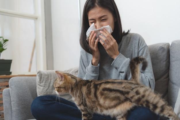 Maladies du concept d'animaux domestiques. une femme éternue sur le canapé en raison d'une allergie à la fourrure et joue avec son chat. Photo Premium
