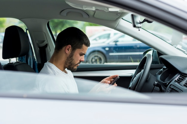 Mâle à l'aide d'un smartphone assis dans la voiture Photo gratuit
