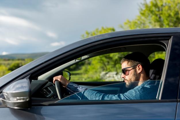 Mâle brutal avec des lunettes de soleil au volant d'une voiture Photo gratuit