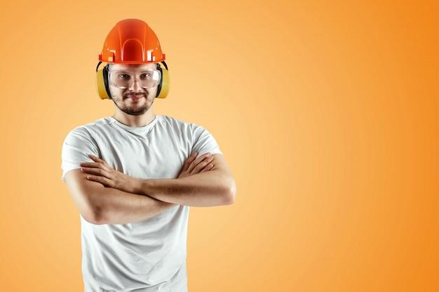 Mâle constructeur en casque orange sur fond orange Photo Premium