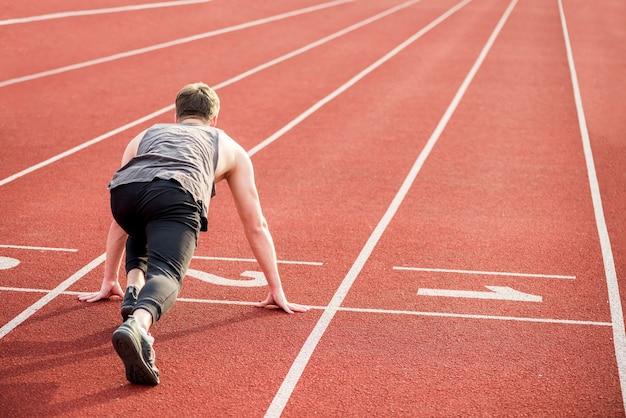Mâle coureur commençant le sprint à partir de la ligne de départ Photo gratuit
