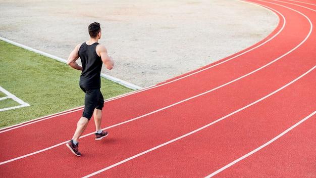 Mâle coureur courir sur piste de course rouge Photo gratuit