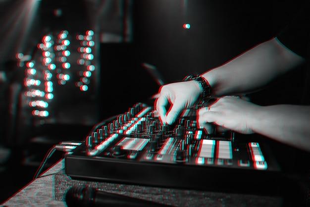 Male Dj Mixe De La Musique électronique Sur Un Contrôleur De Musique Professionnel Dans Une Discothèque Lors D'une Fête. Photo Premium