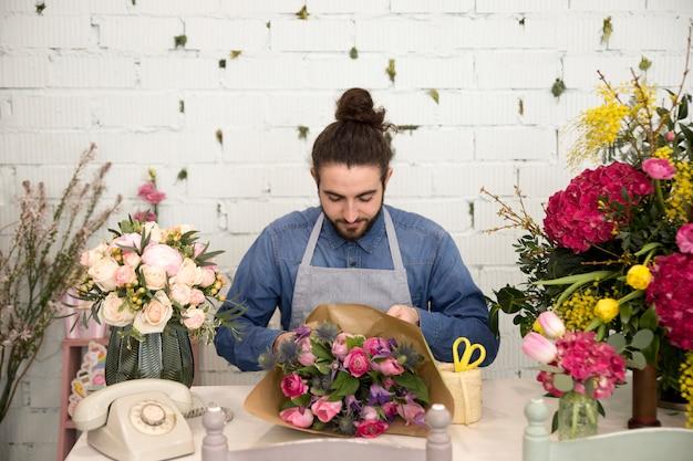Mâle fleuriste envelopper le bouquet de fleurs dans le papier à son magasin de fleurs Photo gratuit