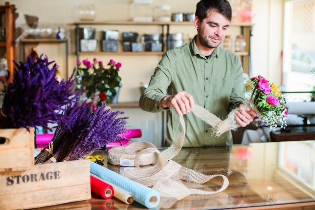 Mâle fleuriste faisant un bouquet dans un magasin de fleurs Photo Premium