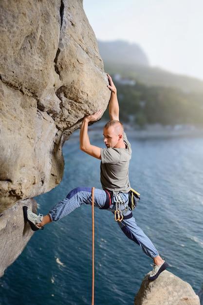 Mâle grimpeur escalade gros rocher dans la nature avec une corde Photo Premium