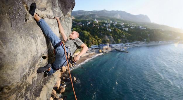 Mâle grimpeur faisant difficile monter sur la falaise en surplomb Photo Premium