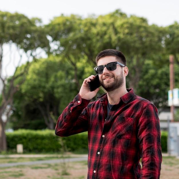 Mâle, lunettes soleil, communiquer smartphone Photo gratuit