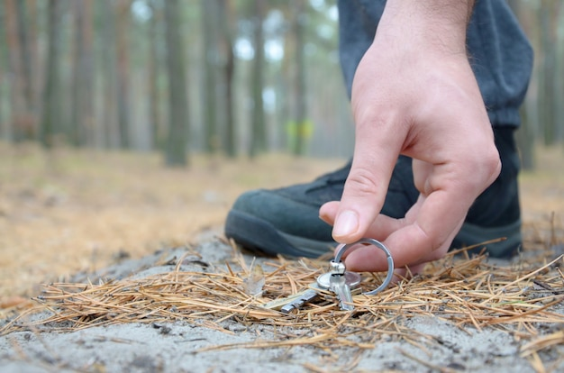 Mâle Main Ramasser Les Clés Perdues D'un Sol En Automne Chemin De Bois De Sapin. Le Concept De Trouver Une Chose Précieuse Et Bonne Chance Photo Premium