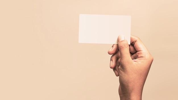 Mâle main tenant une carte de visite vierge sur un fond vintage pour le texte. Photo Premium